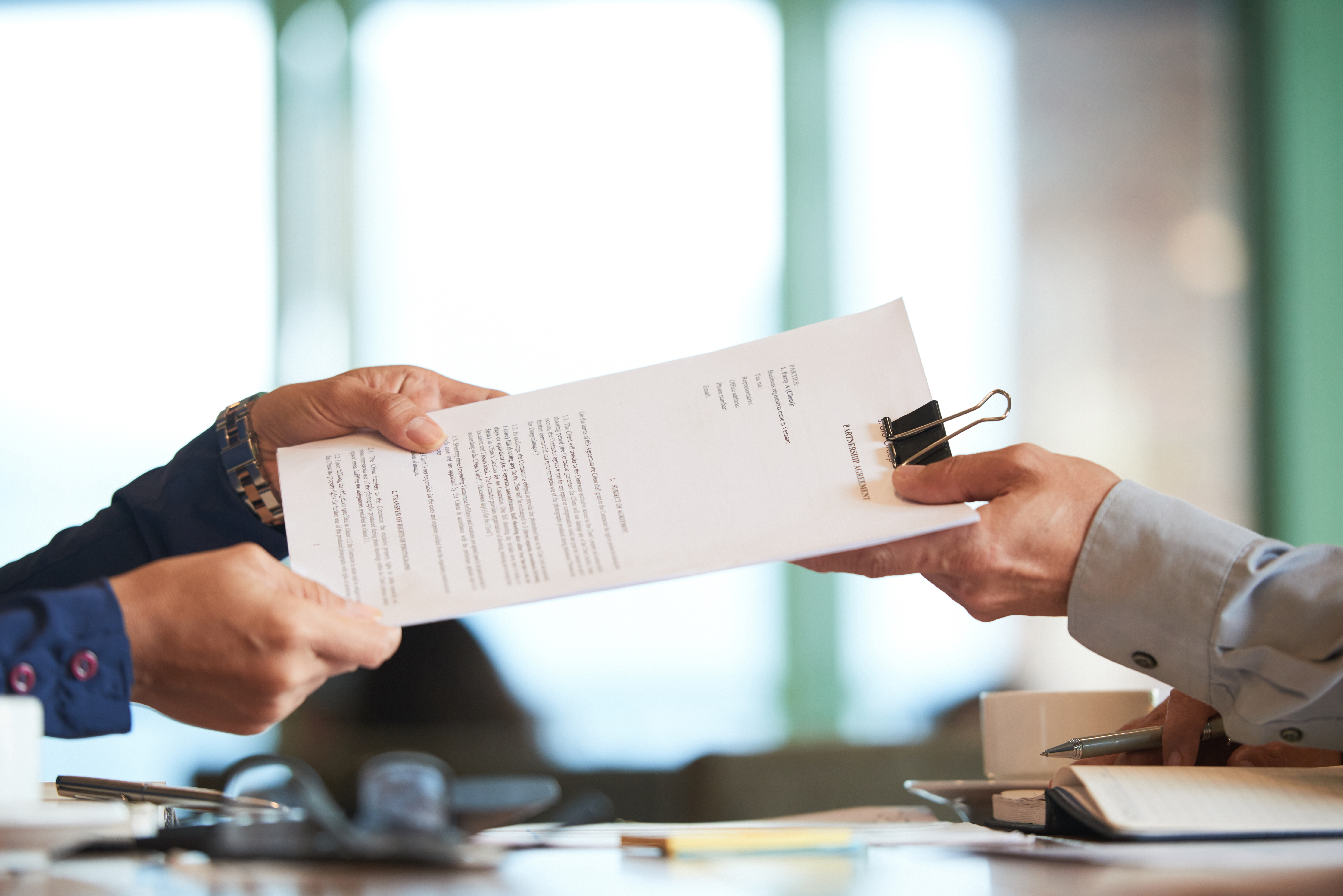 Business person giving partnership agreement to coworker